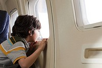 Boy looking through window on an airplane