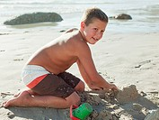 Boy making sandcastles on a beach