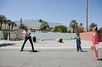 Father playing ball with son and daughter
