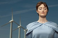 Woman with eyes closed at wind farm