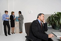 Businessman at desk with others gossiping by water cooler (thumbnail)