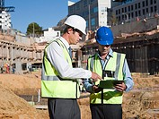 Mature men with clipboard on construction site