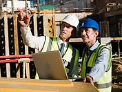 Mature men with laptop on construction site
