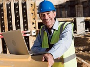 Mature man with laptop on construction site