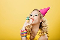 Young woman wearing party hat with party streamer (thumbnail)