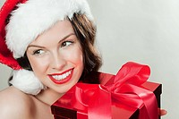 Young brunette woman wearing Santa hat with Christmas present (thumbnail)