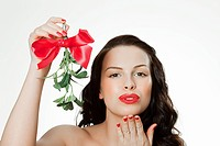 Young woman blowing a kiss holding mistletoe