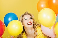 Young blonde woman with balloons against yellow background
