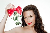 Young woman holding mistletoe