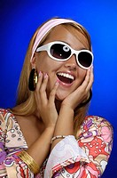 Young fashionable laughing woman in a fancy colorful outfit and sunglasses with funny happy expression Conceptual closeup portrait Isolated on blue ba...