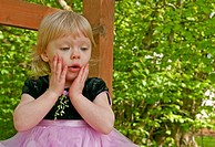 This stock image shows a two year old toddler girl outdoors in a pink princess dress with a surprised expression on her face Her little hands are on h...
