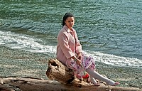 This pretty multi ethnic woman conveys many emotions, sadness, dejected, lonely as she's sitting on driftwood at a beach, with some red carnation flow...