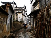 Man carrying wooden buckets walking in an alley, Wuyuan, Jiangxi Province, China