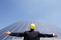 Architect, hard hat, solar cells, standing, gesture, portrait, back view, outside,