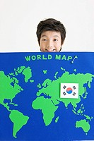 boy holing map of the world