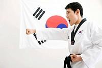 man in Taekwondo uniform in front of Korean flag, Taegeukgi