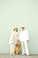 Mature man and wife posing with their dog