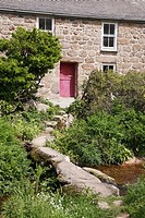 Old stone built cottage with a clapper bridge crossing the stream in front of it Cornwall, England