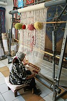 A woman making or weaving a carpet or rug at Kairouan Tunisia North Africa