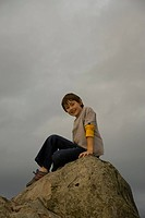 a boy sits on a large rock