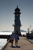 Thailand, People Walking Out On A Pier Towards A Lighthouse