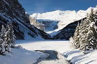 lake louise, alberta, canada, mount victoria in winter with snow covered trees and open water in a creek