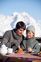 Mother and daughter eating on balcony at ski resort