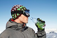 Young man in ski wear drinking water from a bottle, profile