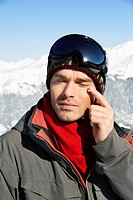 Young man in ski wear applying moisturizer on his face