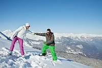 Young couple of skiers on slope