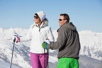 Young couple of skiers looking away