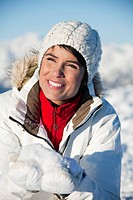Young smiling woman holding snow