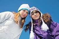 Two teenage girls in winter clothes, smiling at camera