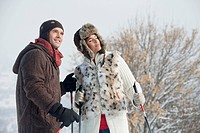Young couple in winter clothes with ski poles