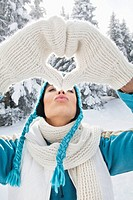 Young woman in winter clothes making heart shape with hands