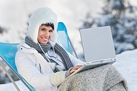 Young woman using laptop computer in snow (thumbnail)