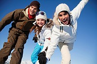 Couple and daughter in ski wear smiling at camera (thumbnail)