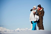 Couple and daughter in ski wear looking away