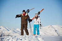 Father and daughter carrying skis