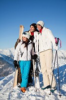 Couple and daughter holding skis, looking away