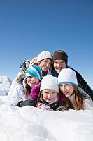 Happy family lying in snow, smiling at camera