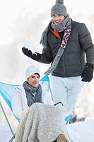 Young man about to throw snowball at woman resting