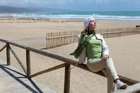 Woman in Barbate beach and wooden barriers supposed to hinder the sand from invading the promenade. Barbate. Cádiz province. Andalusia. Spain