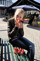 Young girl eating one of the seasons first strawberries