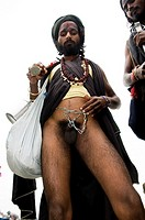 A Naga sadhu showing off his self mutilation.