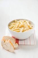 Penne in a bowl, white bread