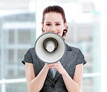 Confident businesswoman yelling through a megaphone standing in the office