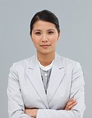 Serious businesswoman with folded arms looking at the camera
