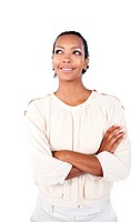 Beautiful businesswoman with folded arms looking up against a white background