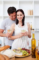 Portrait of a smiling couple cooking and toasting with wine in the kitchen